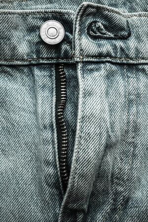 Denim blue jeans button and zip close-up. Casual jeans clothing in demin material, photographed in studio with low-key illumination. 写真素材