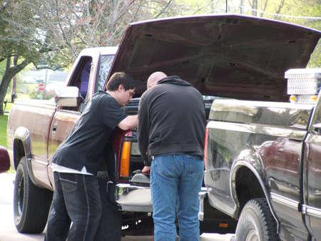 Waterloo,Iowa,April 13 2012 : Teenage boy and man fixing an old pickup truck. Stock Photo - 13161545