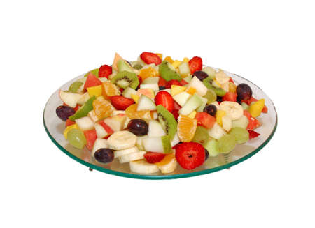 Fruit salad on glass plate . Fruits are bite size . White isolated backround photo