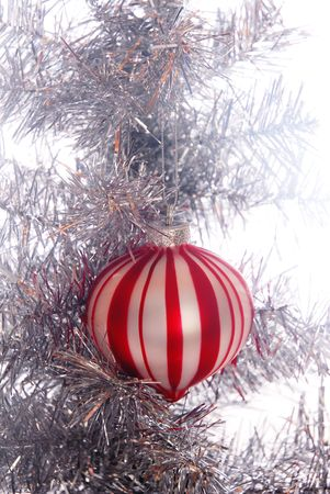 Single red and white stripped ornament hanging in an old style aluminum Christmas tree Zdjęcie Seryjne