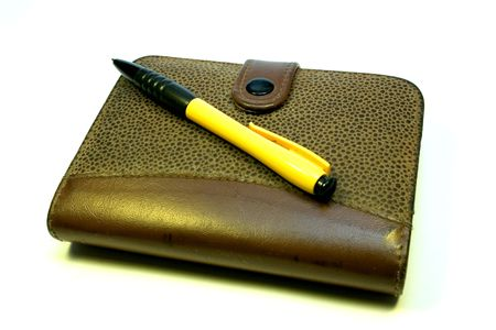 yellow-black ball-point pen on a notebook with leather flight Standard-Bild