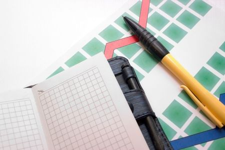 yellow-black ball-point pen on the graphic coloured diagram with a notebook