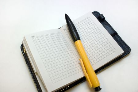 yellow-black ball-point pen in hand on a notebook with leather flight Standard-Bild