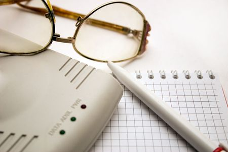 modem, notebook, pen and glasses on a light background