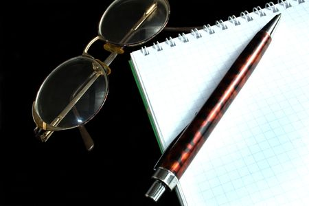 glasses, pen and notebook on a black background