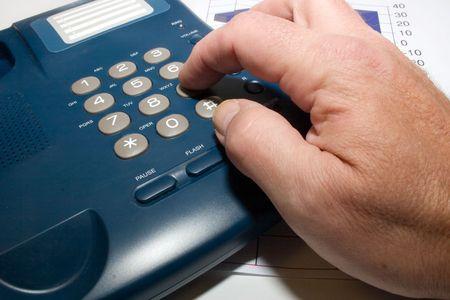 a hand dials up on a telephone set Standard-Bild