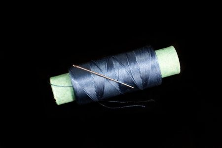 Spool with threads and iloy on a black background