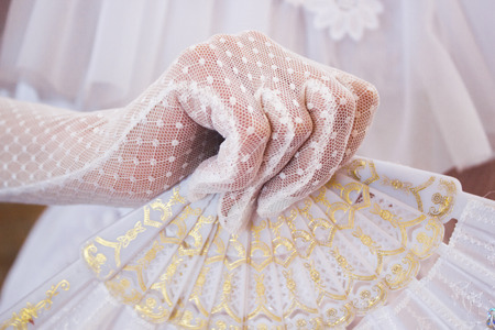 Girl in a lush white dress and in white gloves with beautiful hand fan during costumed dance party in retro style Stock Photo