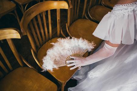 Chica en un vestido blanco exuberante y en guantes blancos con ventilador de mano hermosa durante la fiesta de baile disfrazado en estilo retro