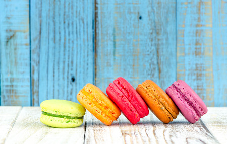 confections: Colorful macarons on vintage pastel background. Macaron or Macaroon sweet meringue-based confection.