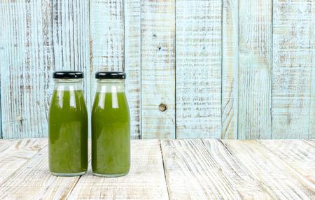 juice bottle: Kiwi juice bottle on vintage wooden background Stock Photo