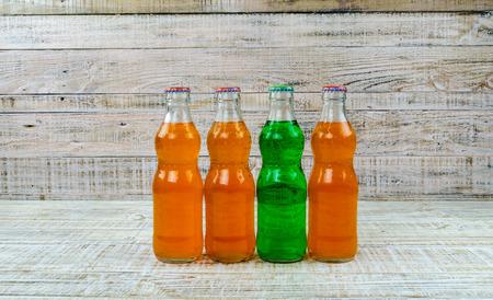 agua con gas: variedad de botellas de soda en el fondo de madera Foto de archivo