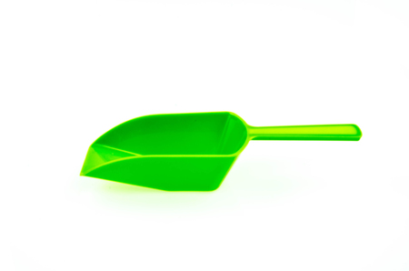 factitious: A simple bright green plastic spoon on white background