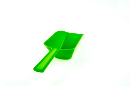 gaudy: A simple bright green plastic spoon on white background