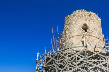 Old stone tower under reconstruction. Repair scaffolding