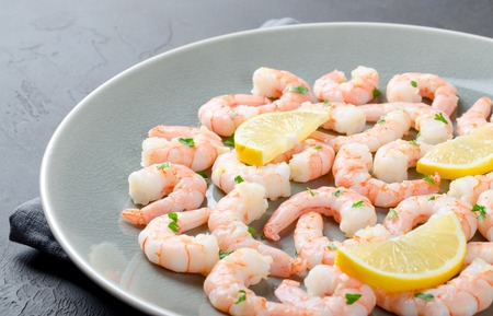 Gray plate full of peeled roasted prawns made with garlic and ginger sauce, served with lemon slices on a dark stone background, close-up