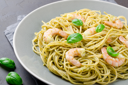 A plate with spaghetti and prawns on a black stone table