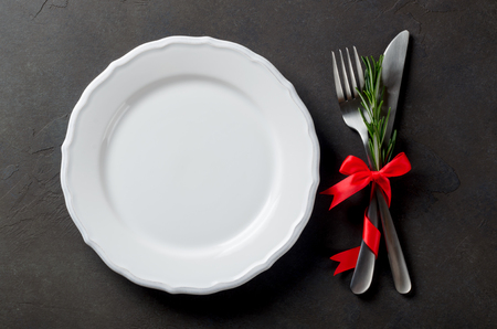 Festive set of cutlery knife and fork with red satin bow and rosemary, a white dessert plate, dark stone slate background, top view, copyspace Stock Photo
