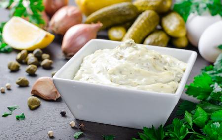Zelfgemaakte traditionele Franse saus remoulade in een witte kom met ingrediënten, citroen, eieren, sjalot ui, augurken, peterselie, mosterd op een zwarte achtergrond van de donkere steen leisteen. Horizontaal