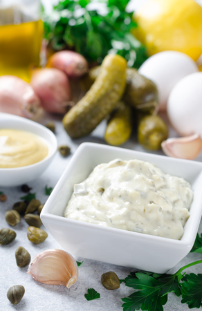Homemade traditional french sauce remoulade in a white bowl with ingredients, lemon, eggs, shallot onion, pickles, parsley, mustard on a light stone background. Vertical Standard-Bild