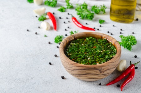 A wooden bowl wirh homemade fresh chimichurri sauce standing on a wooden board with ingredients