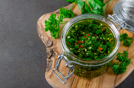 A glass jar wirh homemade fresh chimichurri sauce standing on a wooden board with herbs on a background