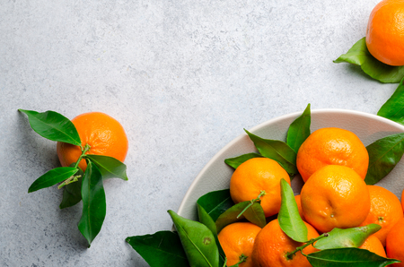 Fresh clementines on a gray plate on a light stone background. Top view, copy space, horizontal image
