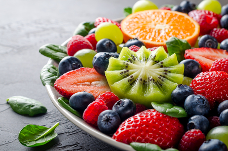 Fruit platter with various fresh strawberry, raspberry, blueberry, tangerine, grape, mango, spinach on a dark black stone background. Copy space, front view, horizontal image