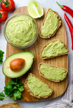 Traditional mexican homemade guacamole sauce in a glass bowl and sliced bread on a wooden board and light stone background. Top view, vertical image