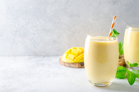 Mango lassi with mint leaves, traditional indian drink in glasses on a light gray stone table. Front view, horizontal image, copy space