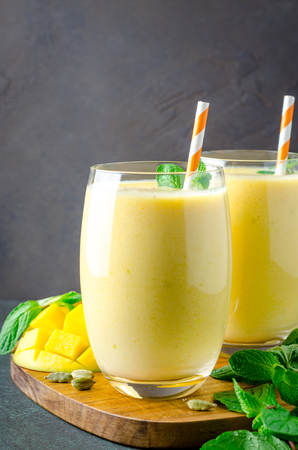 Two glasses of mango lassi with mint leaves and orange straws on a wooden board and dark table. Vertical image, copy space, front view