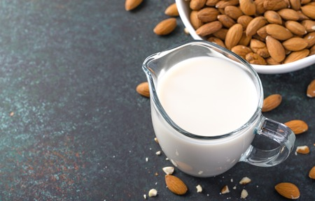 Almond milk in a milk pitcher with almond nuts on a dark stone background. High angle view, horizontal image, copy space 写真素材
