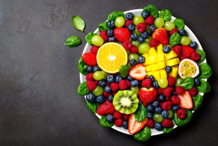 Fruit platter with various fresh strawberry, raspberry, blueberry, tangerine, grape, mango, spinach on a dark black stone background. Copy space, top view, horizontal image 写真素材