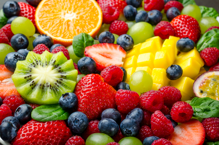 Fruit platter with various fresh strawberry, raspberry, blueberry, tangerine, grape, mango, spinach. Close-up, horizontal image