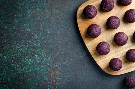 Raw energy balls with acai berry powder on a wooden board on dark background. Horizontal image, copy space, top view