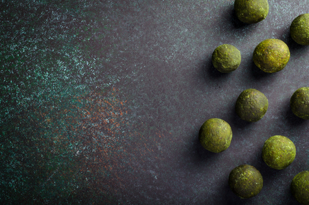Raw energy balls with matcha tea powder on dark background. Horizontal image, copy space, top view 写真素材