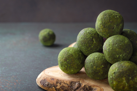 Raw energy balls with matcha tea powder on a wooden board on dark background. Horizontal image, copy space, front view