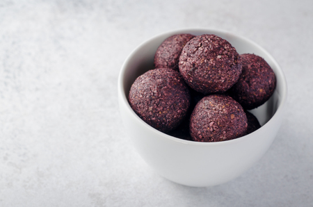 Raw energy balls with acai berry powder in white bowl on a light background. Horizontal image, copy space, high angle view 写真素材