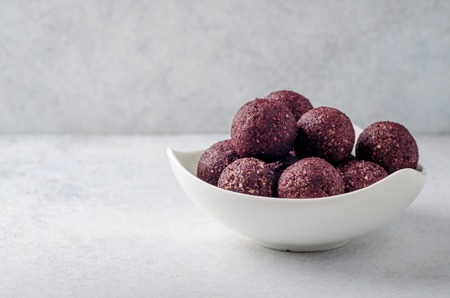 Raw energy balls with acai berry powder in white bowl on a light table. Horizontal image, copy space, front view 写真素材