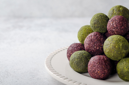 Raw energy balls with acai berry powder and matcha tea on a white plate on a light table. Horizontal image, copy space, front view