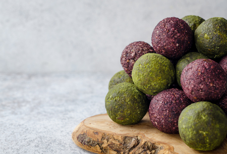 Raw energy balls with acai berry powder and matcha tea on a wooden board on a light table. Horizontal image, copy space, front view