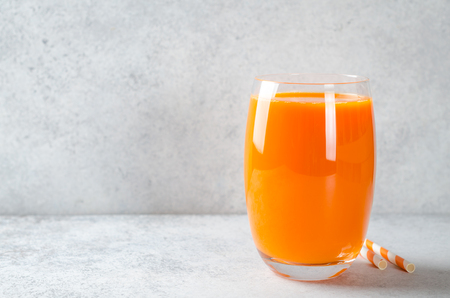 Carrot juice in tall glass on a light gray table, horizontal image, front view, copy space