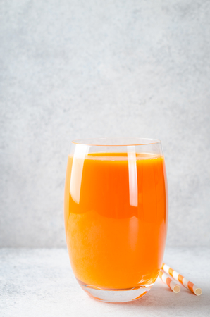 Carrot juice in tall glass on a light gray table, vertical image, front view, copy space 写真素材