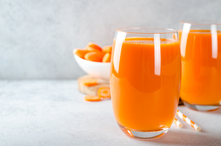 Carrot juice in tall glasses on a light gray table, horizontal image, front view, copy space