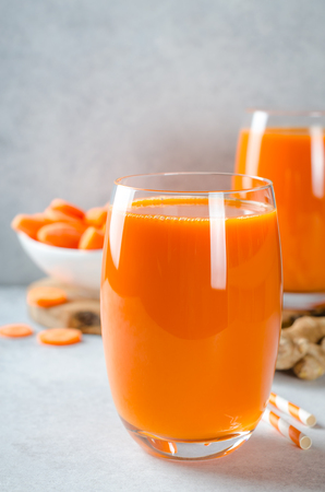 Carrot juice in tall glasses on a light gray table, vertical image, front view, copy space 写真素材