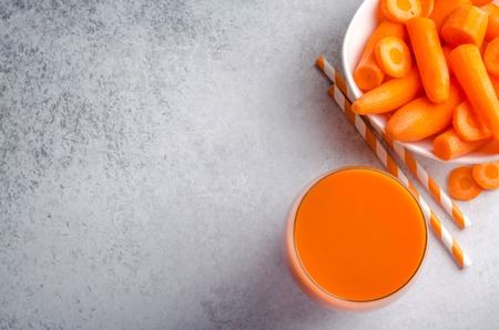 Carrot juice in tall glasses on a light gray table, horizontal image, top view, copy space