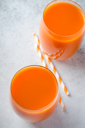 Carrot juice in tall glasses on a light gray table, vertical image, high angle view, copy space