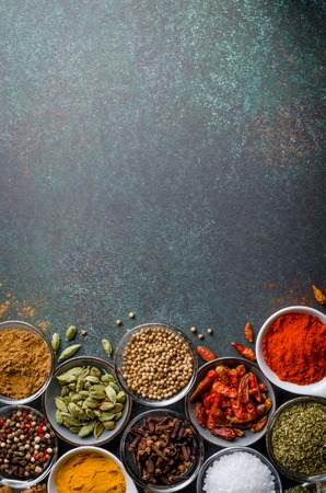 Various spices in glass bowls on a dark stone background with copy space, top view, vertical image