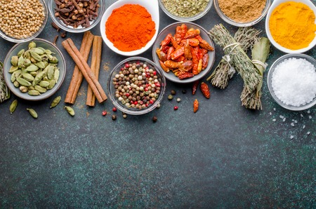 Various spices in glass bowls on a dark stone background with copy space, top view, horizontal image