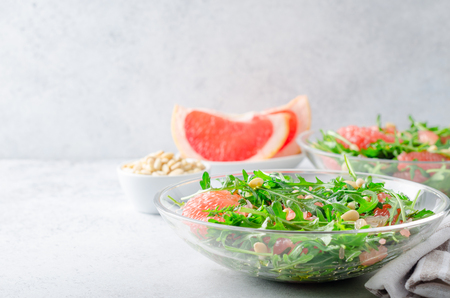 Grapefruit and arugula salad with pine nuts in glass bowls on a light gray stone concrete table. Horizontal image, front view, copy space Stock Photo